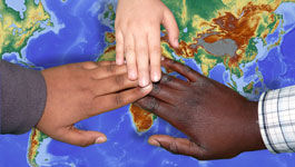 Drei Hände unterschiedlicher Hautfarbe liegen auf einer Weltkarte