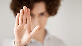 Eine Frau hebt abwehrend die Hand