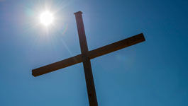 Kreuz mit aufgehender Sonne im Hintergrund