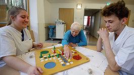 Zwei Auszubildende in der Altenpflege mit einer Bewohnerin