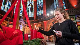 Junge Frau zündet Kerzen am Adventskranz in Kirche an