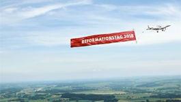 Flugzeug mit Banner Reformationstag