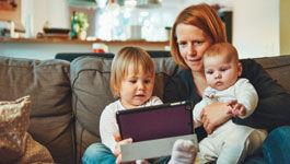 Mutter mit zwei Kindern auf der Couch beim Spielen