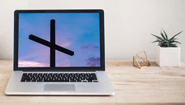 Geöffnetes Notebook mit einem Kreuz auf einem Schreibtisch mit