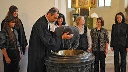 Pfarrer tauft einen jungen Erwachsenen