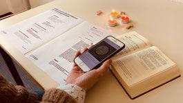 Hand mit Handy und aufgeschlagenem Gesangbuch und Gebetszettelauf dem Tisch