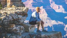 Mann sitzt auf einem Fels und schaut in die Weite