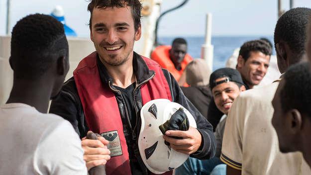 Ein Crew-Mitglied der Sea Watch-2 freut sich mit geretteten Flüchtlingen.