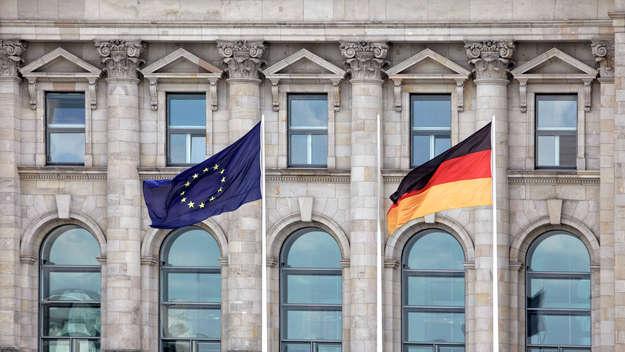 Eine europäische und eine deutsche Flagge wehen vor dem Bundestag in Berlin.