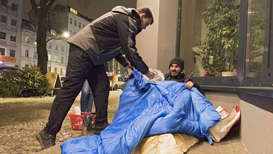 Fahrer des Berliner Kältebus gibt einem Obdachlosen einen Schlafsack