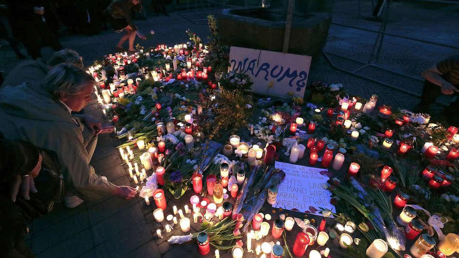 Menschen stellen Kerzen am Ort der Amokfahrt von Münster auf