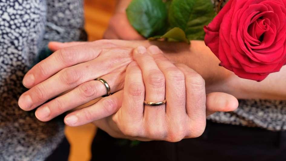 Zwei Frauen halten sich an den Händen