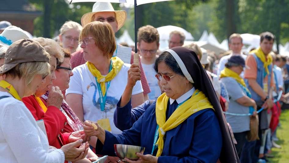 Eine Ordensschwester teilt beim Katholikentag die Kommunion aus