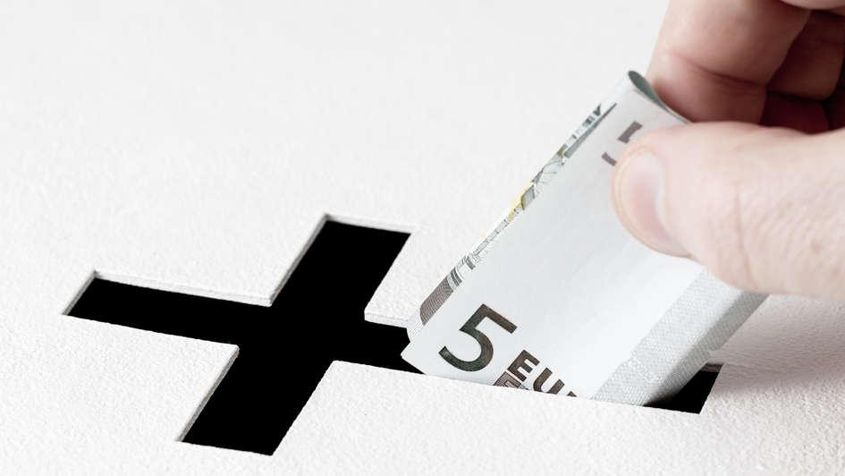 Hand mit Geldschein an Spendenbox.