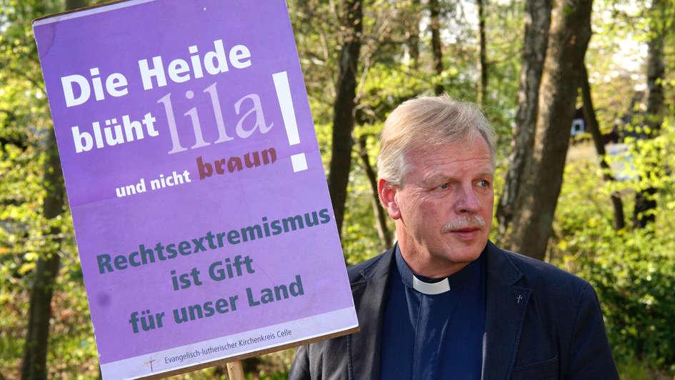 Pastor Wilfried Manneke demonstriert mit Plakat in der Hand in Eschede bei Celle gegen ein Treffen von Neonazis.