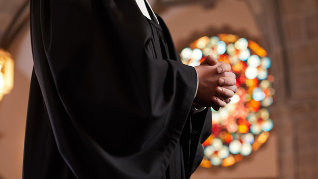 Pastor with folded hands in a church.