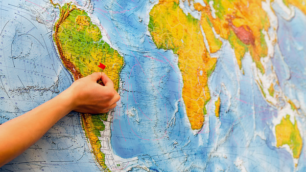Hand with a pin in front of a world map.