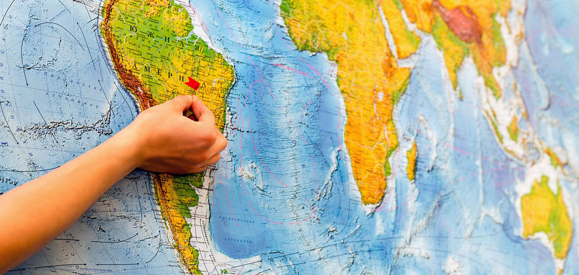 hand with apin in front of a world map.